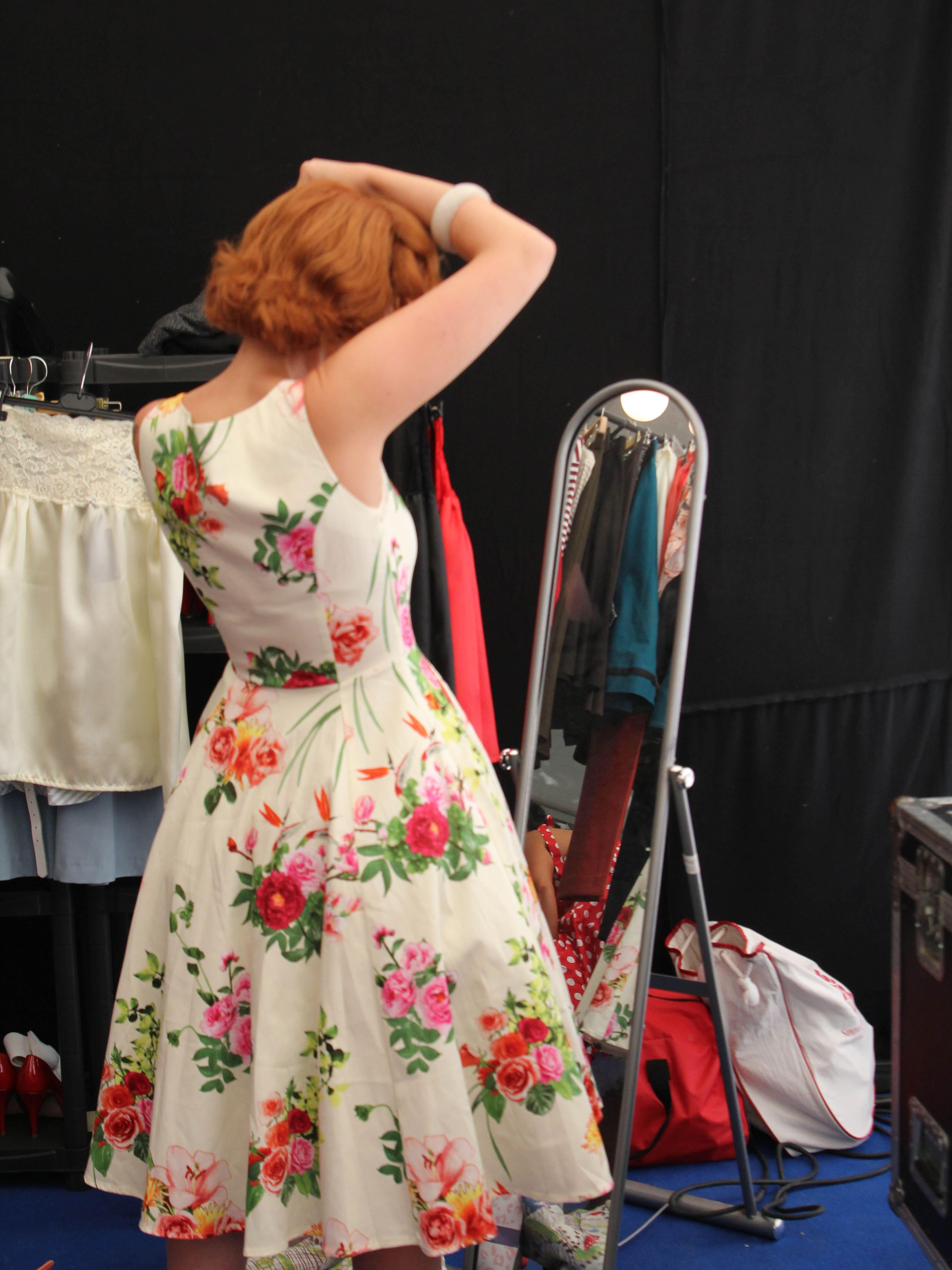 Frau in Vintagekleid vor Spiegel