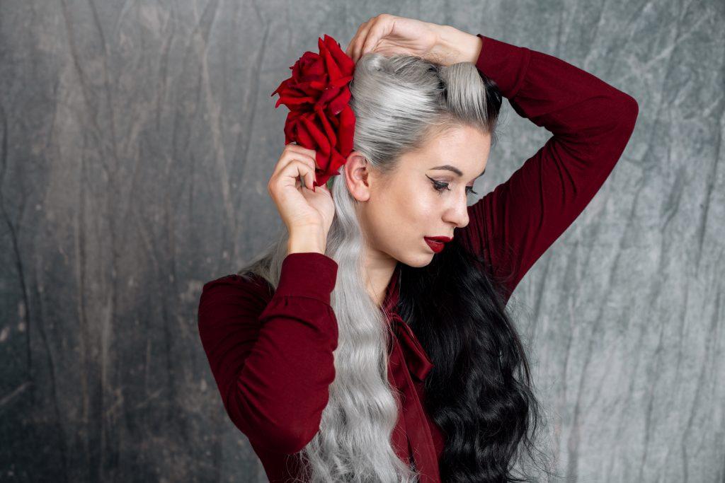 Frau setzt Haarschmuck in Retrofrisur