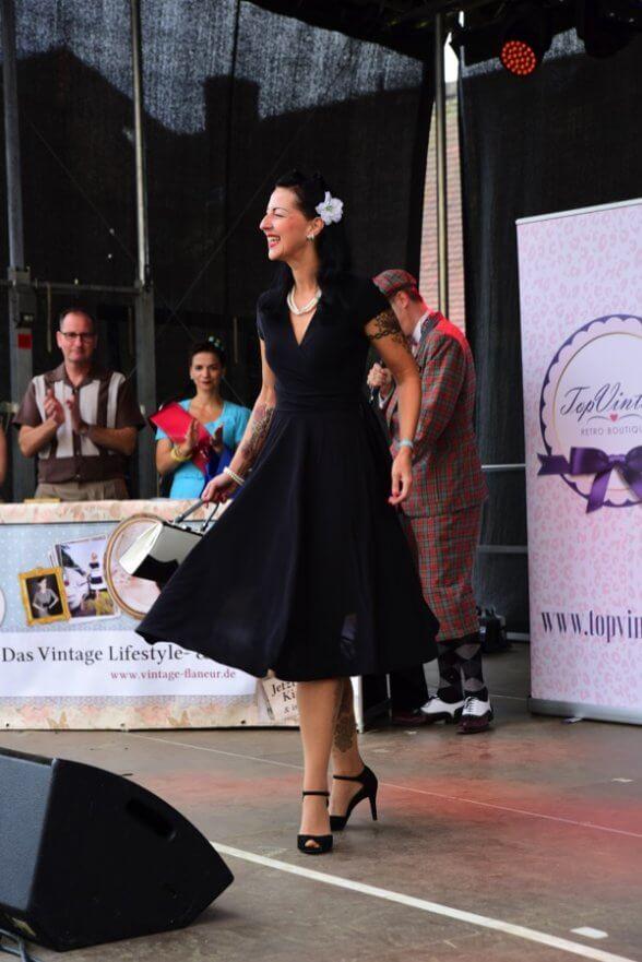 Lilian de la Fleur präsentiert ihr weit schwingendes schwarzes Kleid