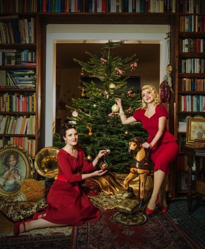 Frauen im Vintagelook schmücken den Weihnachtsbaum