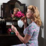 Frau schminkt sich im Retrolook
