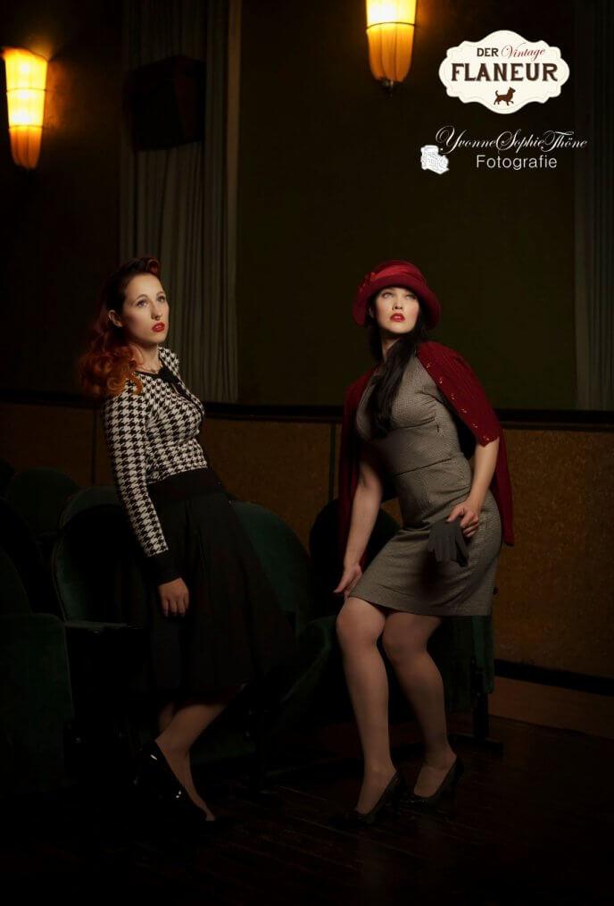 Frauen in Vintagekleidung im Kino klappen Stühle runter