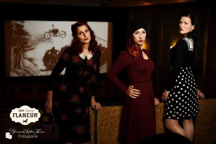 Frauen in Retrokleidung langweilen sich bei Actionfilm