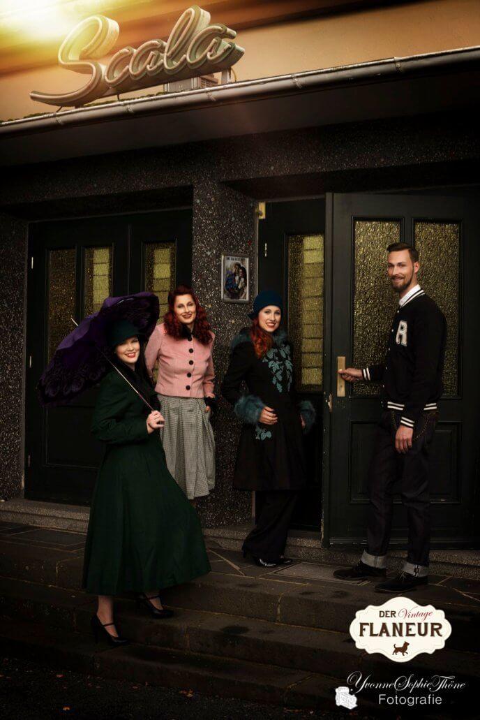 Gruppe von Menschen in Vintage Wintermode betritt ein Kino