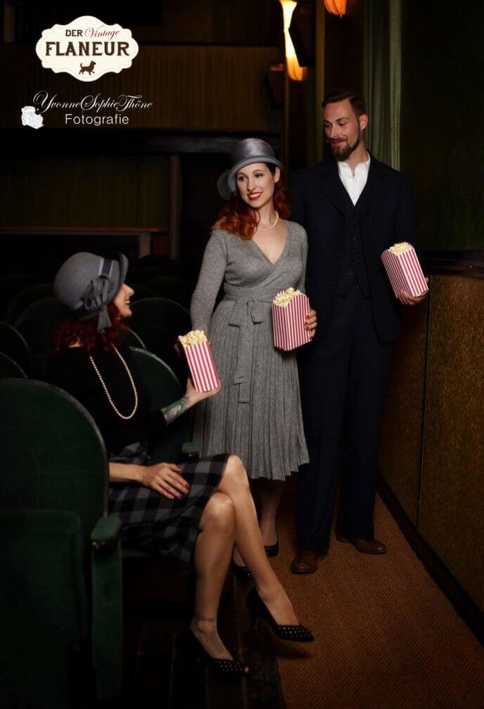 Menschen in Vintagemode im Kino bringen popcorn
