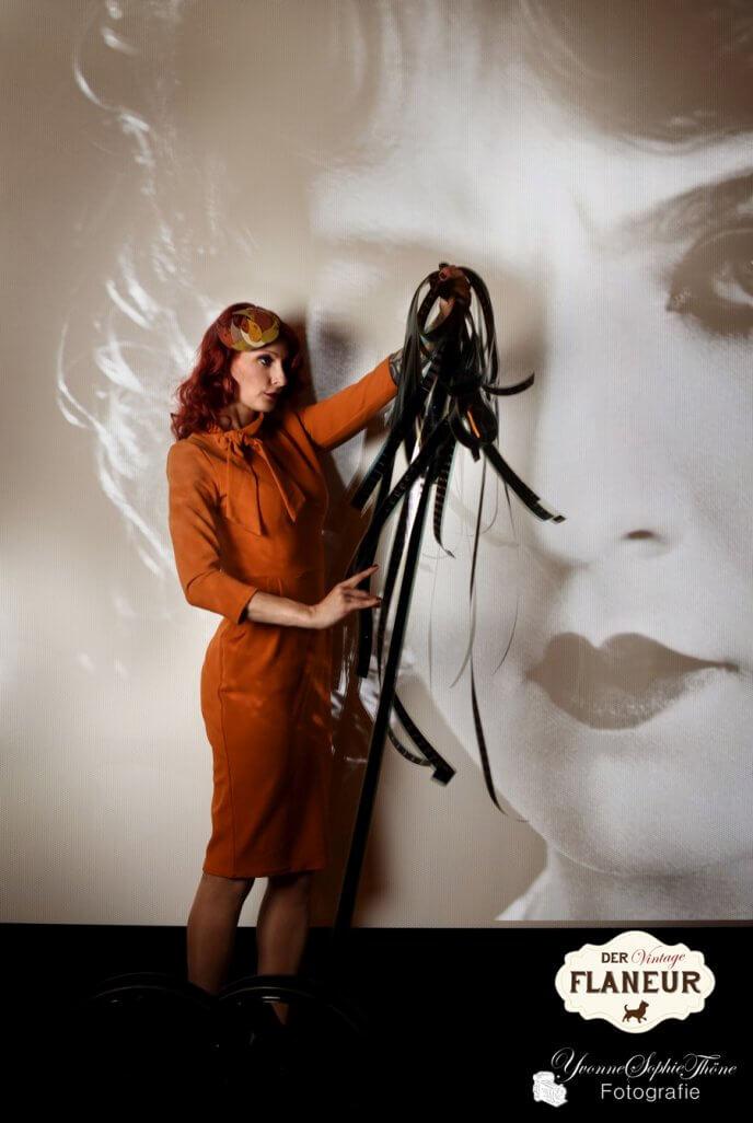 Frau in Retrokleidung vor Kinoleinwand