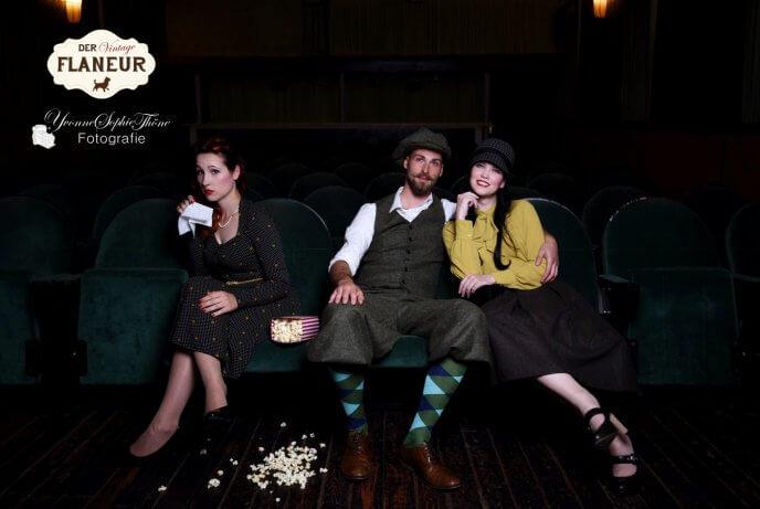 Menschen in Retrokleid und Knickerbocker sitzen im Kino