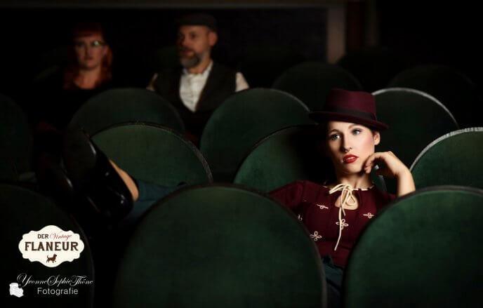 Frau im Vintageoutfit sitzt im Kino