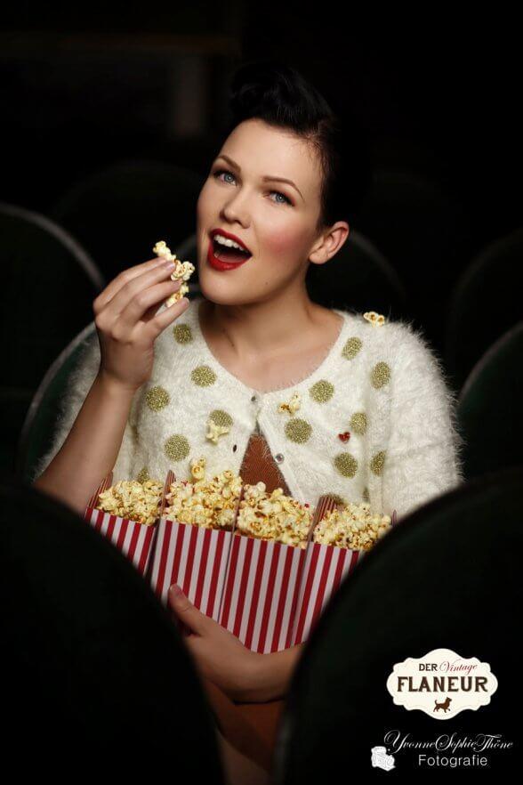 Frau im Vintagelook isst Popcorn