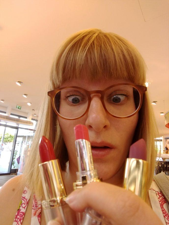 Frau verzweifelt mit vielen Lippenstiften
